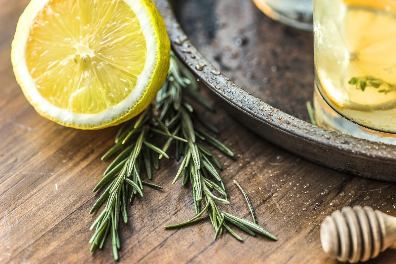 Zitronen und Rosmarin neben einem Glas